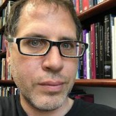 a headshot-style picture of Timothy Schroeder, with a bookshelf in the background